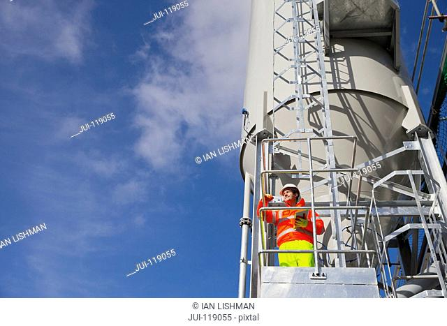 Engineer wearing hi viz protective clothing working on cement processing plant using digital tablet