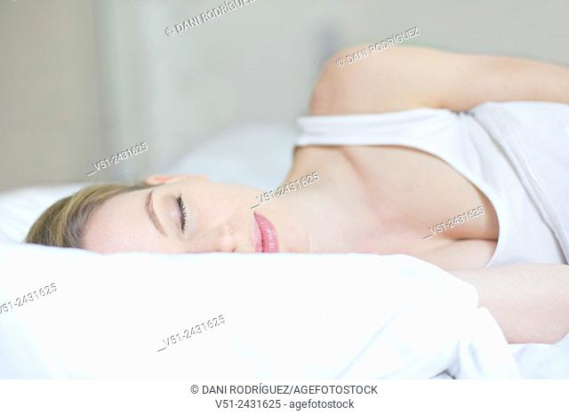 Pretty blonde woman sleeping in bed