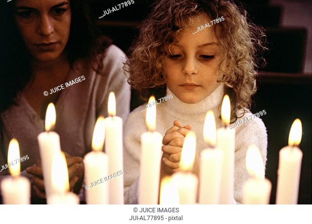 Close up of lit candles with woman and child praying