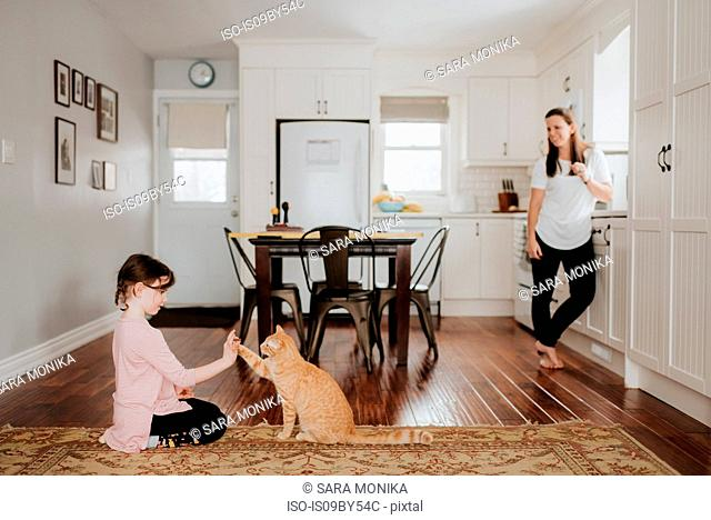 Mother watching daughter play with cat at home
