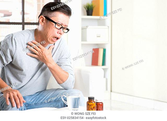 Portrait of casual 50s mature Asian man coughing, pressing on chest with painful expression, sitting on sofa at home, medicines and water on table
