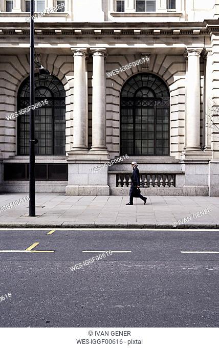 UK, London, senior businessman walking on pavement
