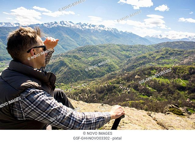 Man Sitting on Top of Mountain with Panoramic View