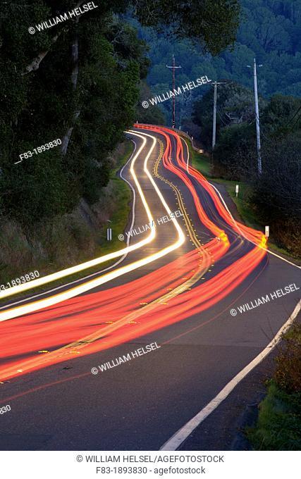 Point Reyes-Petaluma Road, Marin County, California, USA, with car headlight and tail light streaks at dusk