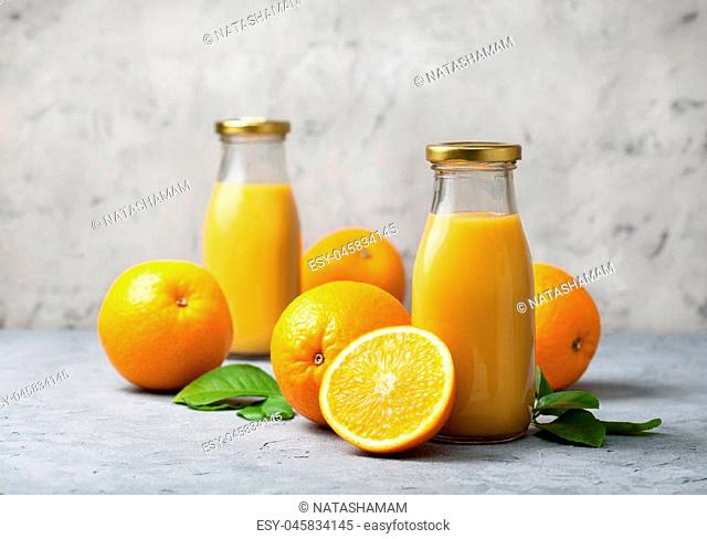 orange juice in glass bottles, fresh oranges on a gray concrete background