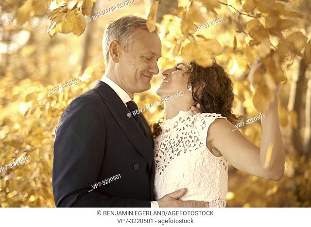 Just married couple between autumn leaves, Starnberg, Bavaria, Germany