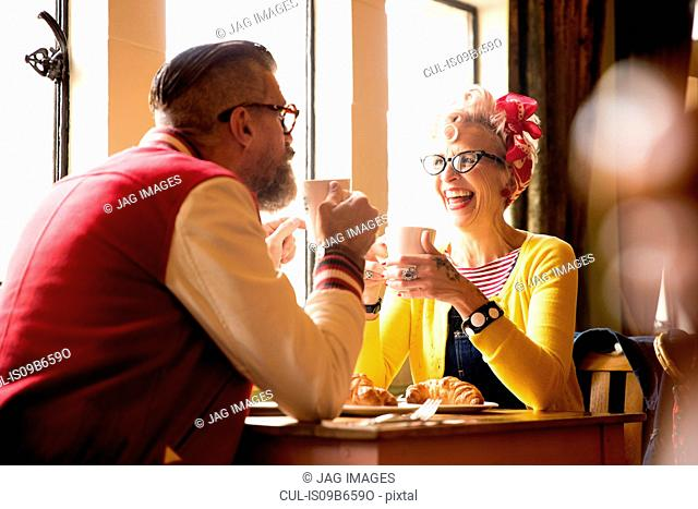 Quirky couple relaxing in bar and restaurant, Bournemouth, England
