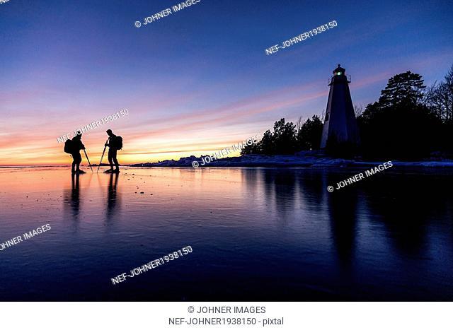 People long-distance skating at evening, Vanern, Sweden