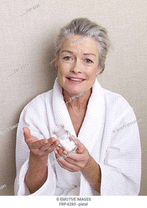 Senior woman wearing bathrobe holding medicine