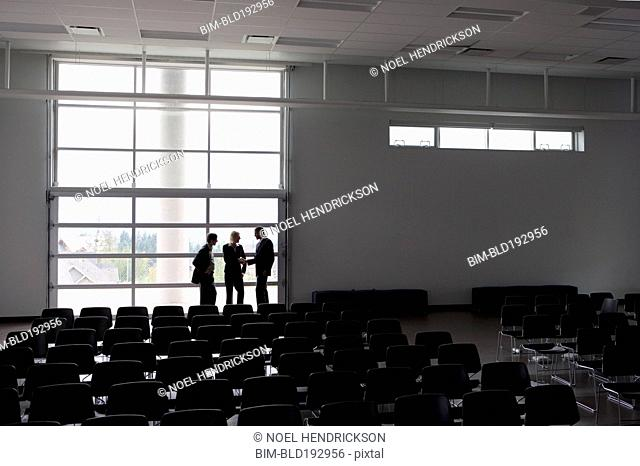 Business people talking in empty auditorium