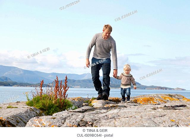 Man and son strolling by fjord, Aure, More og Romsdal, Norway