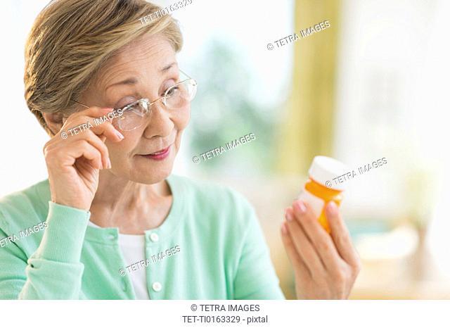 Senior woman reading medicine label
