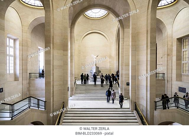 Tourists on staircase at Louvre