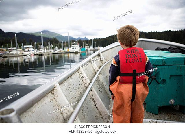 Young boy stands in his family's set-net skiff with a life vest saying 'kids don't float', South-central Alaska; Seldovia, Alaska, United States of America