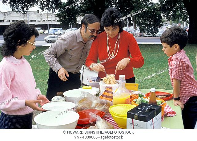 Family of four in the park with father supervising the serving of spaghetti at the picnic table