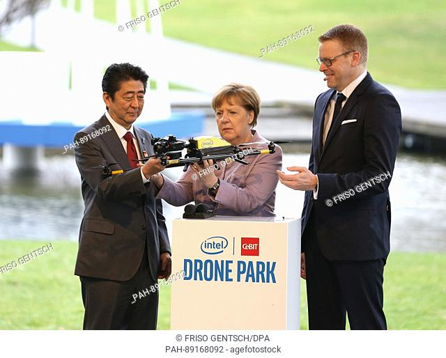 German Chancellor Angela Merkel and Japanese Prime Minister Shinzo Abe (L) look at a drone on the intel stand during their tour of the CeBIT trade fair in...