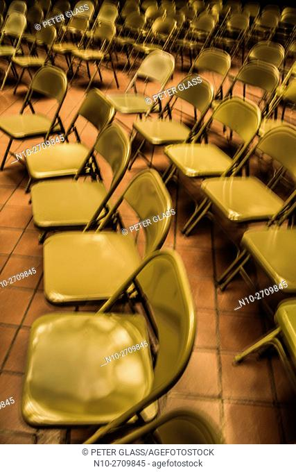 Empty folding metal chairs in an auditorium