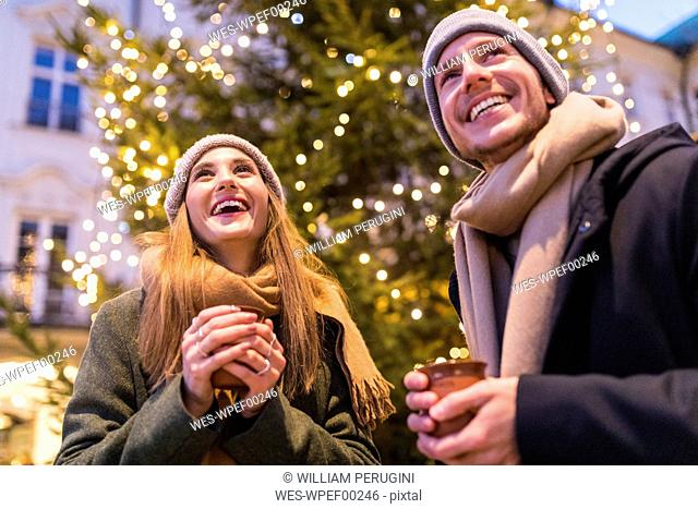 Laughing young couple drinking mulled wine at Christmas market