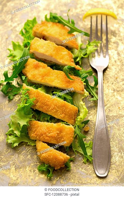 A gluten-free chicken escalope on a bed of lettuce