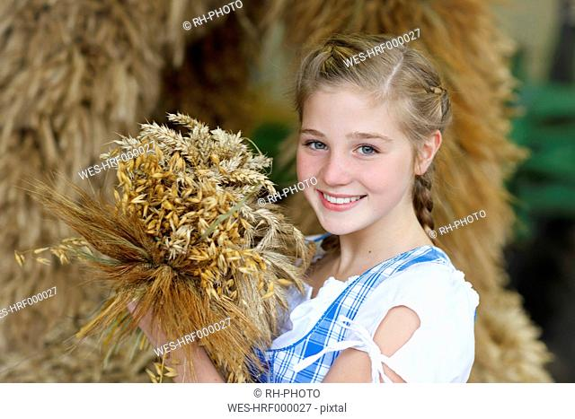 Germany, Luneburger Heide, portrait of smiling blond girl holding bunch of spikes