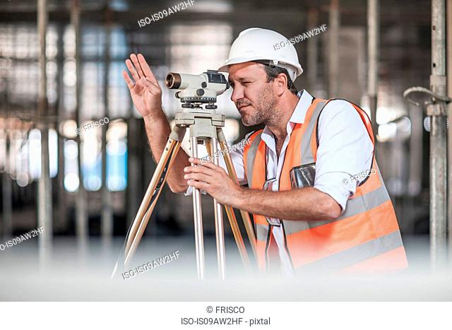 Male surveyor looking through theodolite on construction site