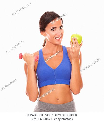 Slim young woman holding apple and dumbbell while looking at you on isolated background