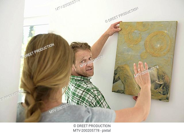 Woman helping man hanging painting wall