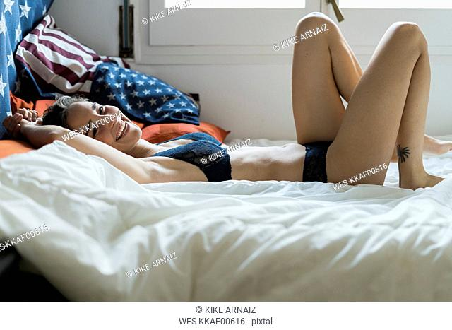 Laughing young woman in lingerie lying in bed