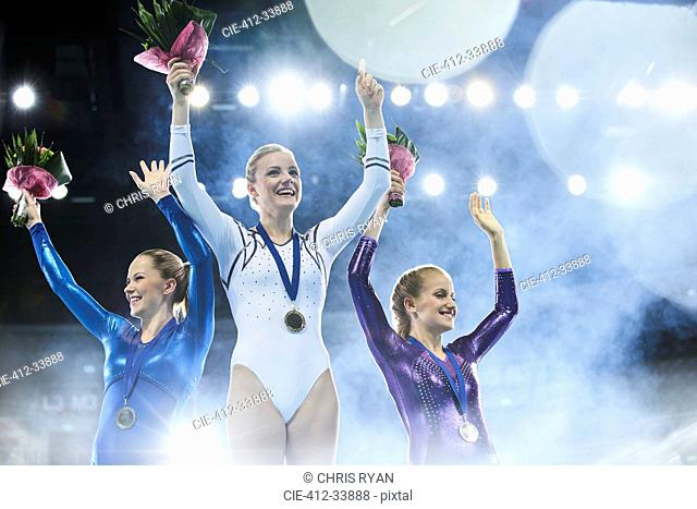 Female gymnasts celebrating victory waving on winners podium