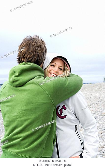 A couple hugging on the beach