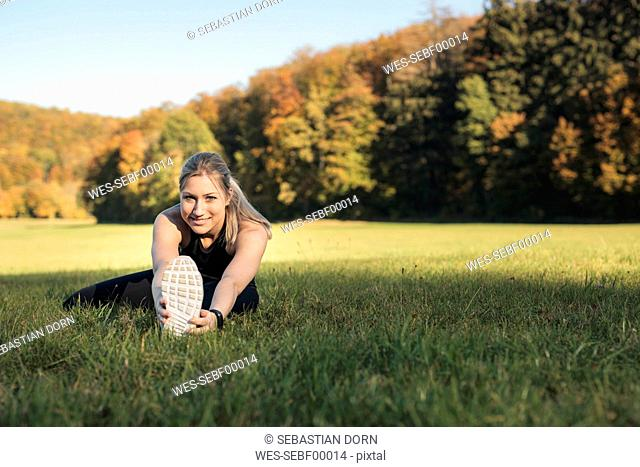 Young woman stretching her leg on a meadow
