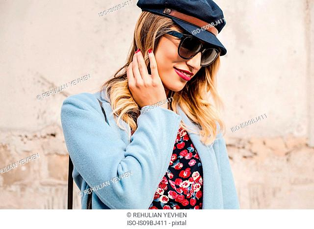 Portrait of woman wearing sunglasses and baker boy cap looking away