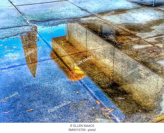Office building and closed umbrella reflected in a puddle on the concrete ground of the patio after a rain