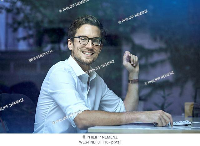 Portrait of smiling young man behind windowpane sitting at his office desk