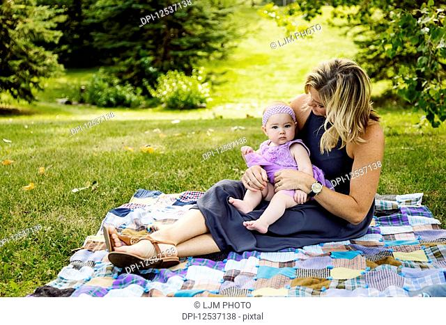 A mother and her baby daughter sitting on a picnic blanket and spending quality time together while enjoying a family outing in a city park on a warm fall...