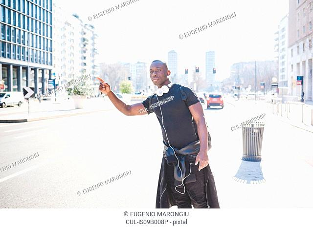 Young man standing by road, hailing cab