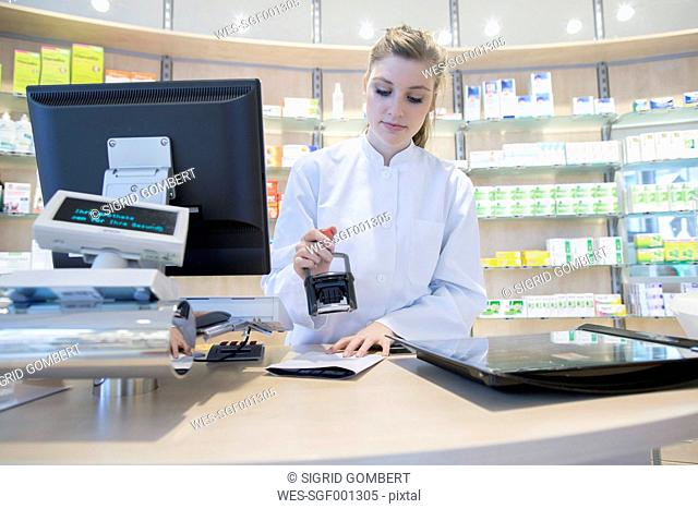 Young pharmacist in pharmacy stamping prescription