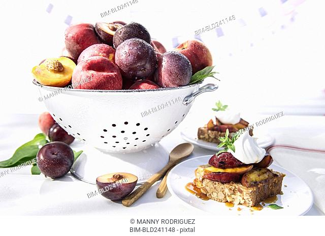 Bowl of fresh fruit in colander with dessert cake