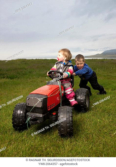 Brother and sister playing on their farmland near Eskifjordur, Iceland