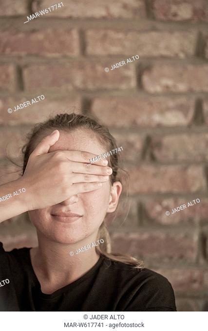 una ragazza si copre gli occhi con una mano