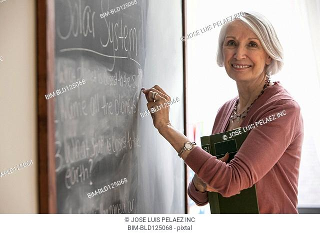 Caucasian teacher writing on chalkboard