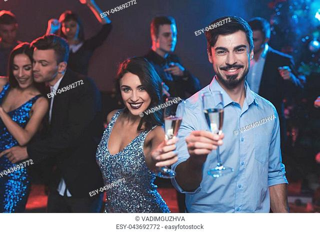 People have fun at the New Year's party. In the foreground, a couple is dancing. They have glasses with champagne in their hands