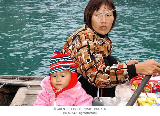 Female trader with child on a boat in Halong bay Vietnam