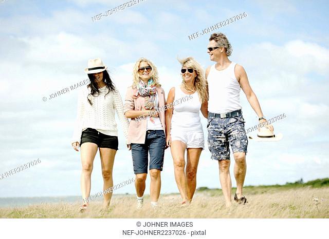 Group of friends walking in field
