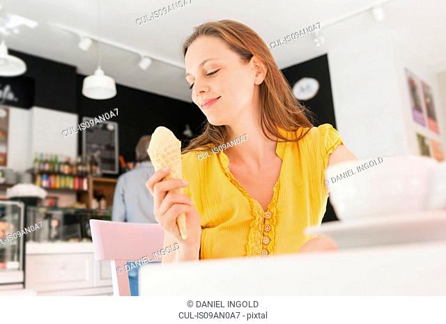 Mid adult woman eating ice cream cone in sidewalk cafe, Sardinia, Italy