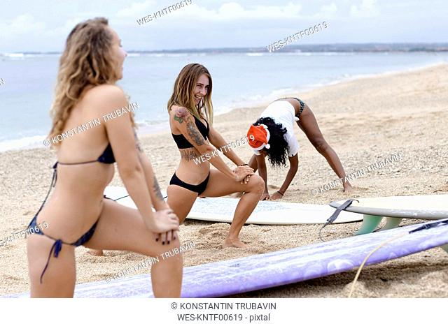 Indonesia, Bali, three women with surfboards on the beach