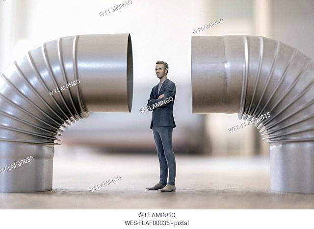 Businessman figurine standing between two stove pipes