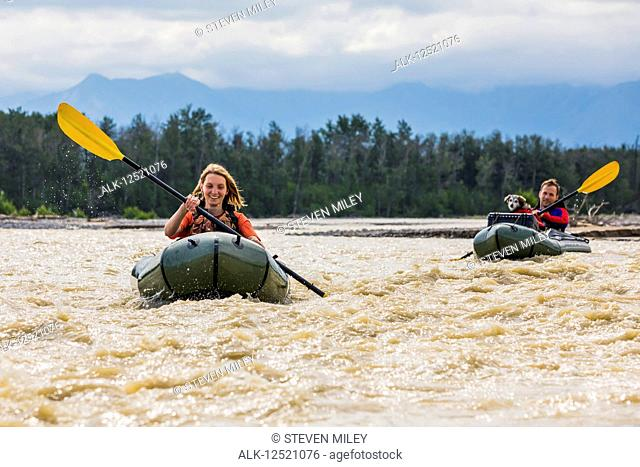 Young couple with their dog in pack rafts in Jarvis Creek, Interior Alaska; Alaska, United States of America