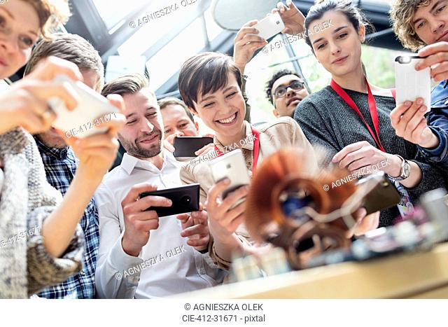 Group with camera phones at technology conference
