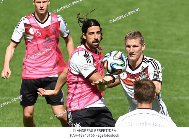 Julian Draxler (from L), Sami Khedira and Bastian Schweinsteiger of the German national soccer team play handball during a training session on a training ground...